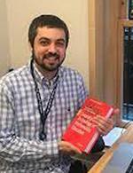 A photo of Dr Benjamin Dickman holding a book